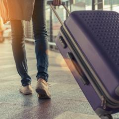 Traveller at the airport with purple suitcase