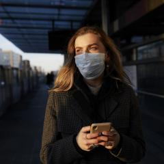 Woman at a train station with mask during COVID-19